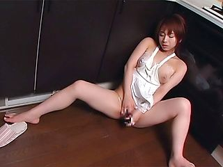 Lovely Asian housewife enjoys solo fingering in the kitchen